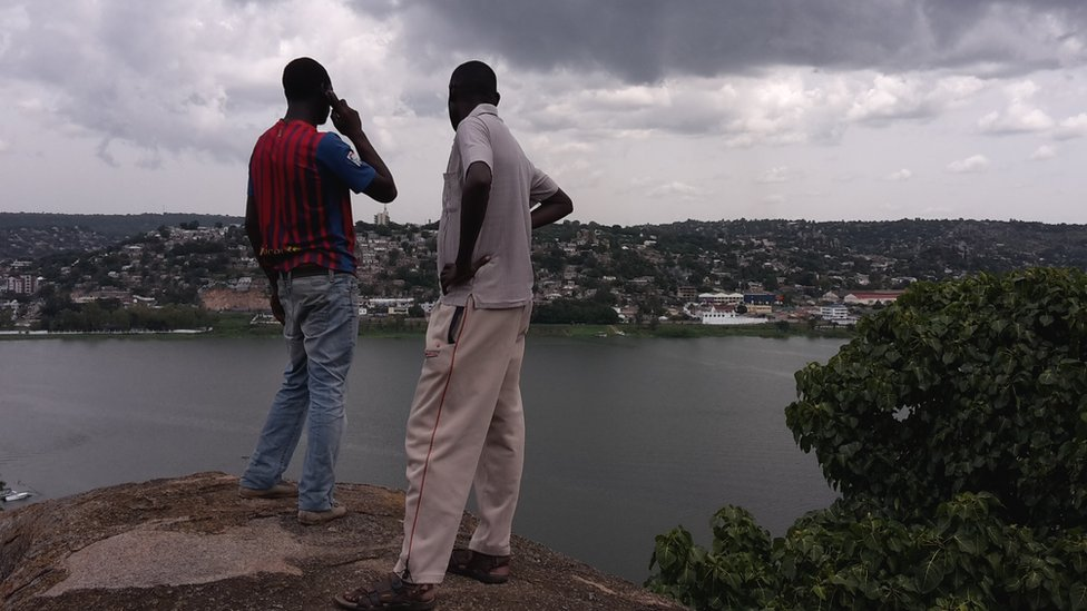 Two people looking over Mwanza, Tanzania one on the phone