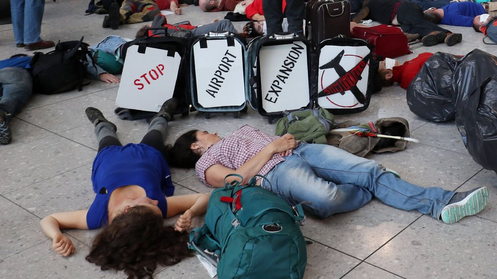 "Campaigners stage a mass ""Die-In"" in Terminal 2 at Heathrow Airport, to protest against aviation expansion ahead of the government's decision on increasing London's airport capacity"
