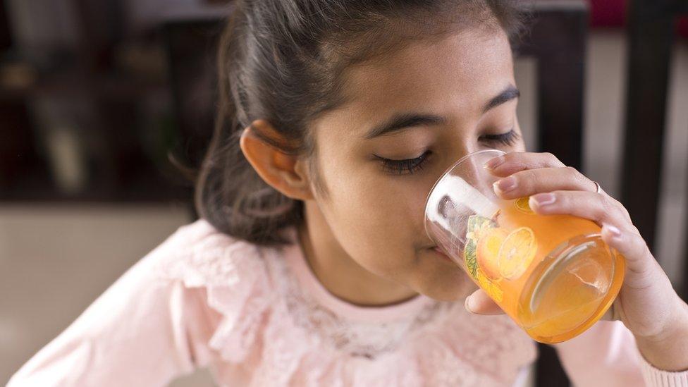 طفلة تشرب عصيرا