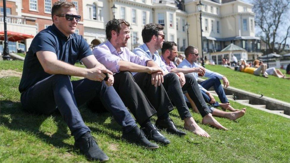Men enjoy the sunshine on Richmond riverside in south-west London
