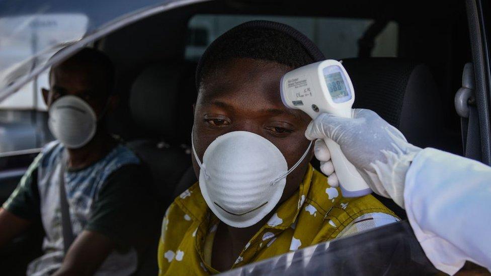 Un miembro del personal del Ministerio de Salud le mide la temperatura a los conductores en una carretera en Kenia.