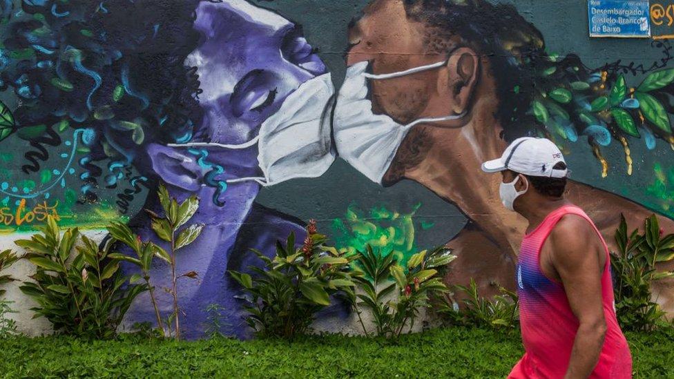 Un hombre con mascarilla camina frente a un mural en el que dos personas pintadas con mascarillas se besan.