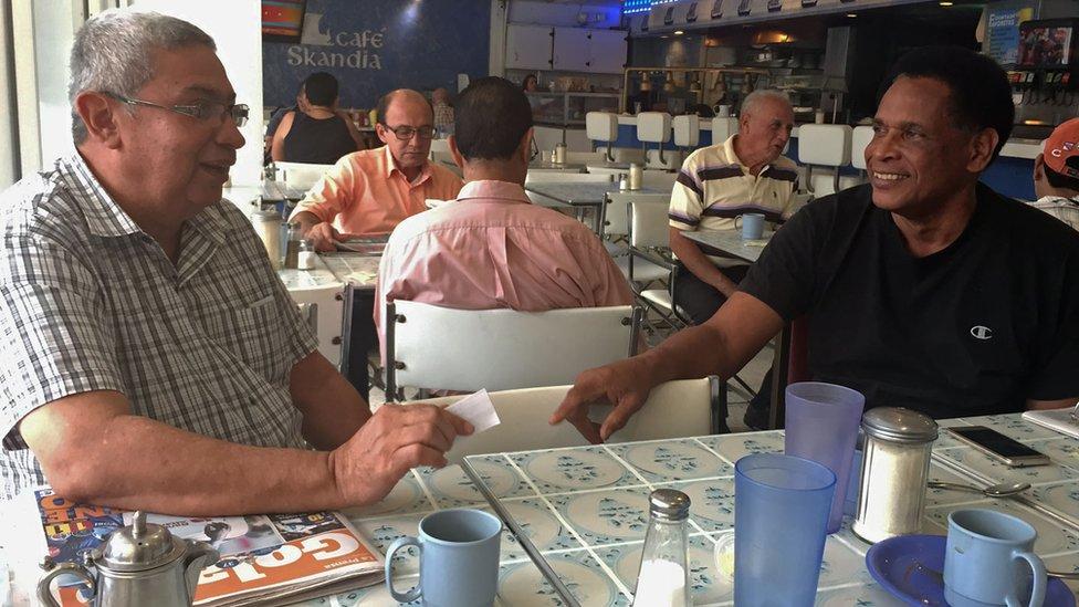 Hombres conversan en tertulia en el café del Gran Hotel Sula
