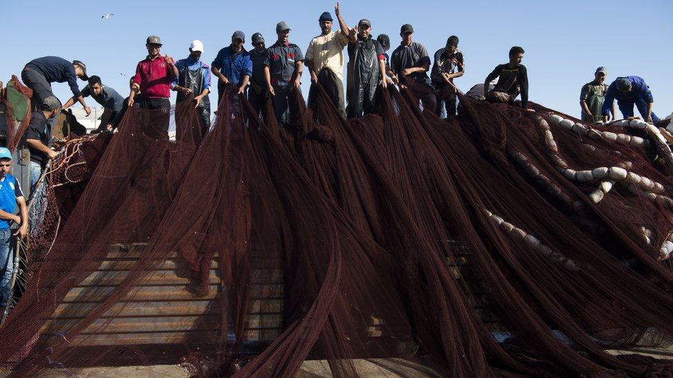 Fishermen arrange their nets.