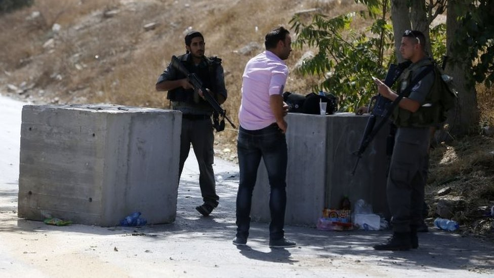 Israeli border guards check the documents of a Palestinian at a roadblock set up in East Jerusalem, on 15 October 2015