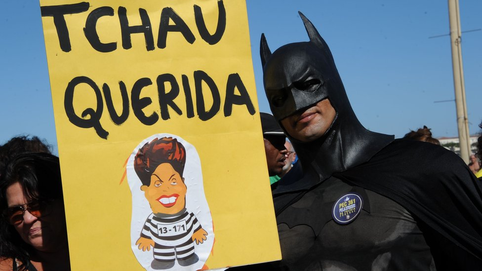 "A man dressed as Batman holds up a sign reading ""bye darling"", referring to President Rousseff"