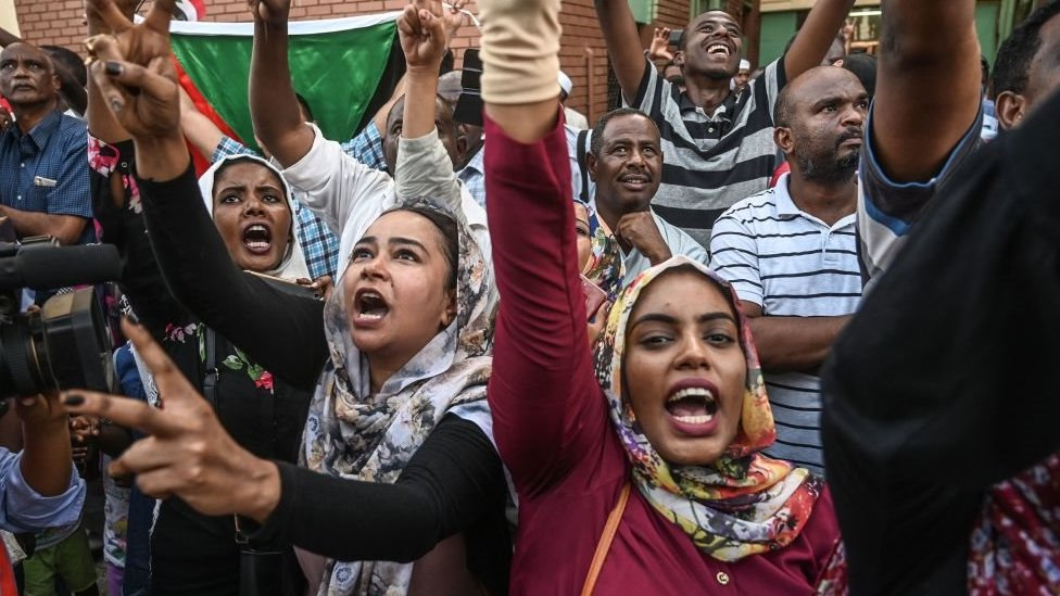 المتظاهرون السودانيون يرحبون بالمتظاهرين القادمين من مدينة عطبرة ويرفعون إشارة النصر في الخرطوم في 23 أبريل/نيسان 2019.