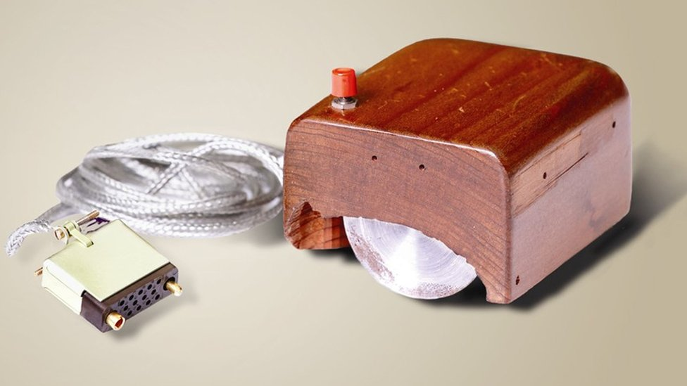 A wooden block with a visible steel wheel underneath, and one single red button, is seen with its cable