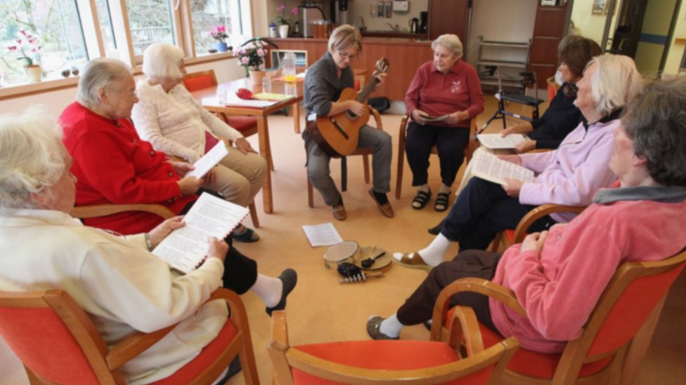 People in a residential care home for Alzheimer's disease and dementia patients sing together with a social therapist