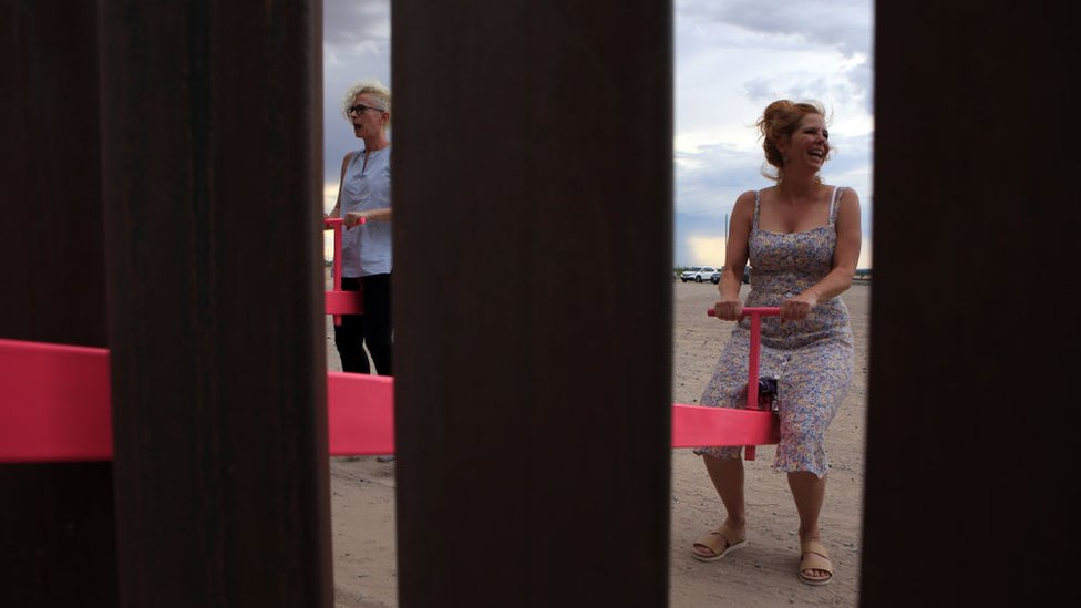 A woman plays on the installation on the Mexican border with the US