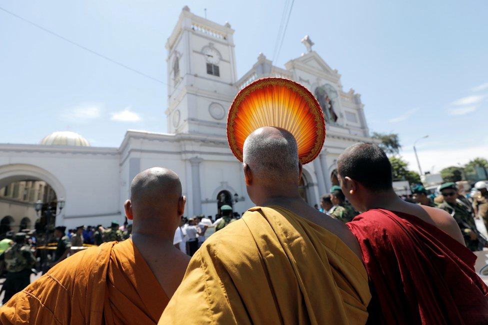Buddhist monks stand in front of the St. Anthony's Shrine, Kochchikade