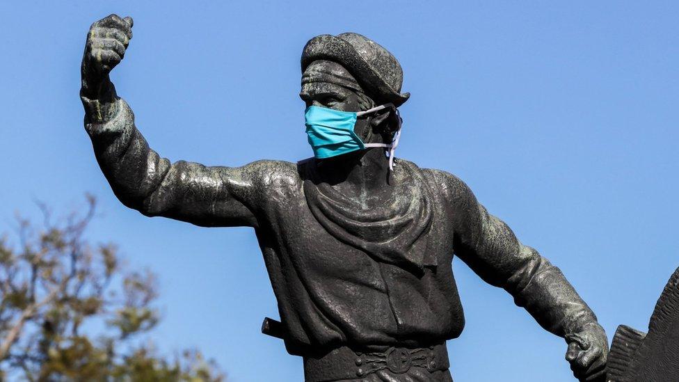 Estatua de gaucho en Montevideo con mascarilla.
