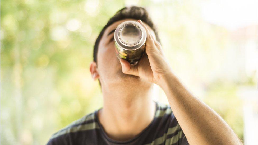 Joven bebiendo de una lata