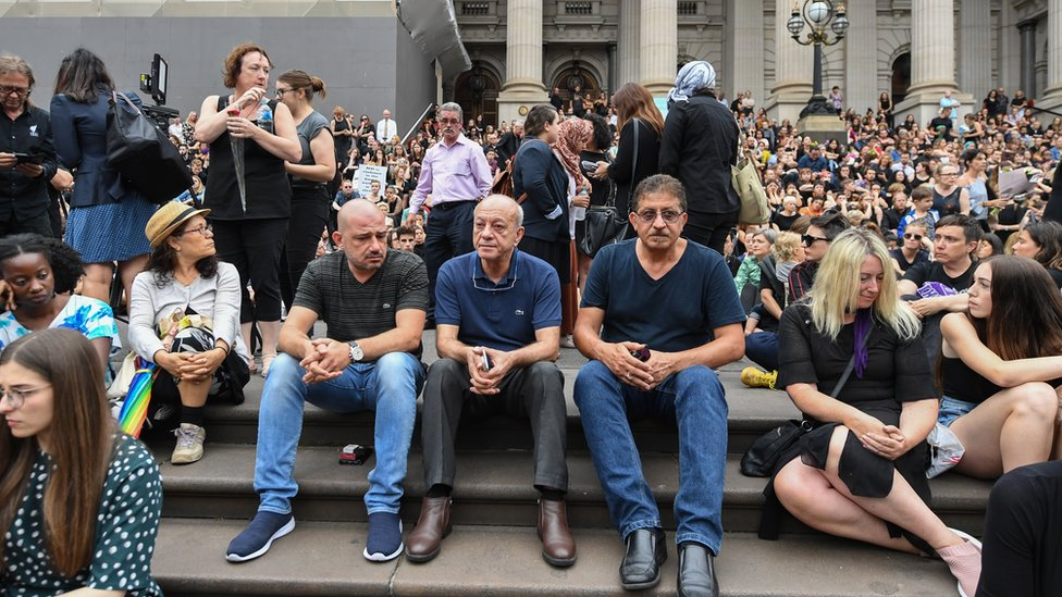 Saaed Maasarwe (centre) sitting down among a crowd of mourners at a vigil for his daughter in Melbourne