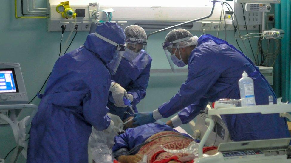 طاقم طبي يطبب مصابا بكورونا