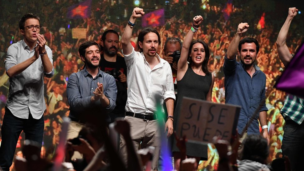 Leader of left-wing party Podemos, Pablo Iglesias (C) raises his fist with left-wing Podemos member and Madrid candidate Irene Montero (2nd R) and Left-wing party IU leader Alberto Garzon (R)