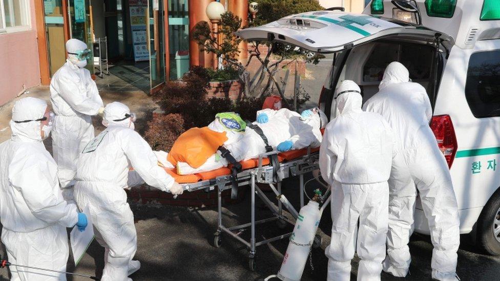 Trabajadores de la salud en trajes protectores trasladan a un paciente de coronavirus en una camilla en Daegu, Corea del Sur