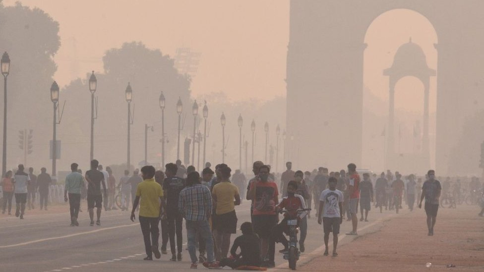 Visitors at a mist covered India Gate, on October 18, 2020 in New Delhi, India
