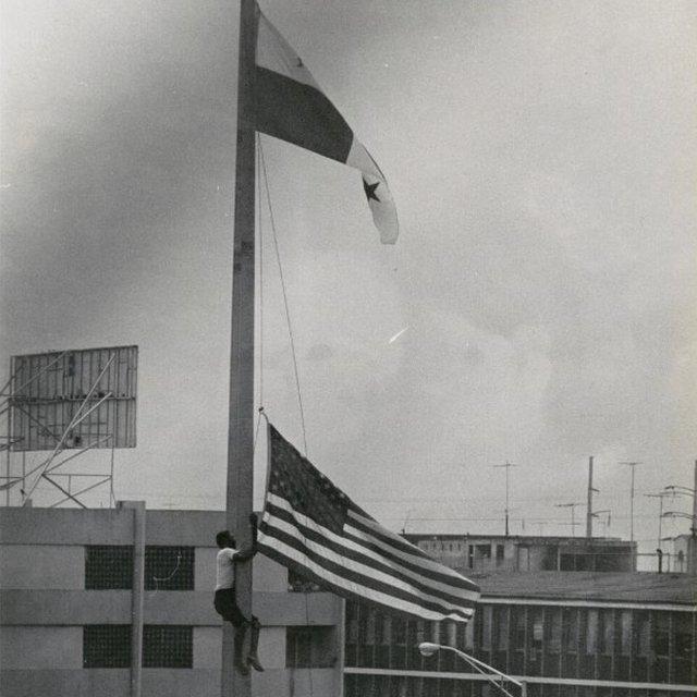 Un joven sustituye la bandera estadounidense por la panameña.