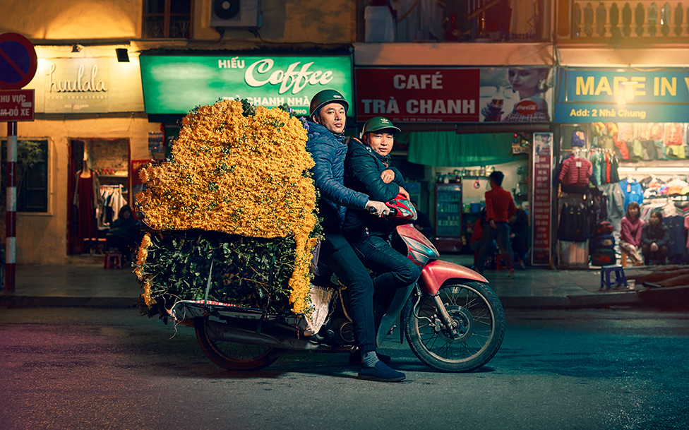 Two men pose on a motorcycle with a large mound of yellow flowers on the back