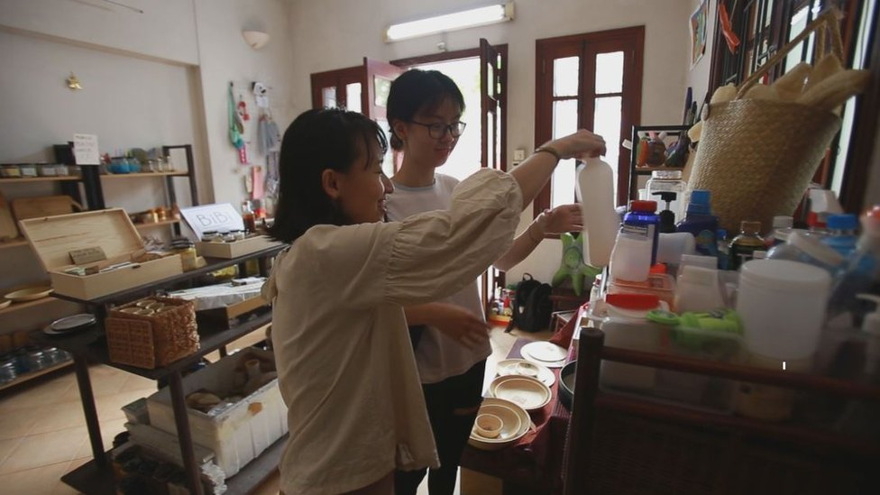 Thao Hoang speaks to a customer in her shop.