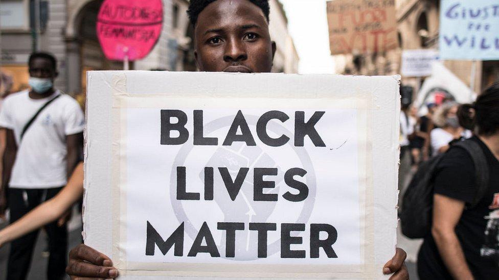 """رجل يحمل لافتة كتب عليها """"حياة السود مهمة"""" خلال احتجاج ضد العنصرية في إيطاليا"""