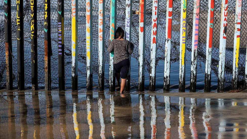 Persona frente a una reja en la frontera entre México y Estados Unidos