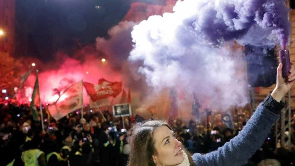 A protester holds a burning flare in Budapest, Hungary. Photo: 16 December 2018