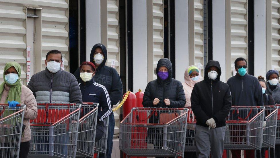 Una fila de compradores todos con mascarillas