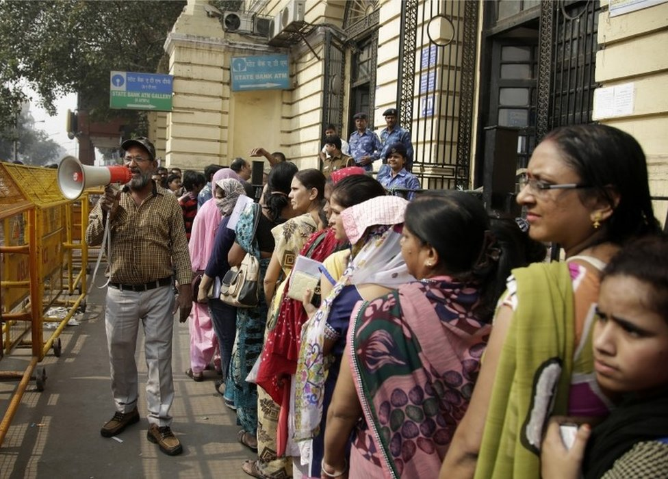 A man, left, holds a megaphone asking people to maintain calm while Indian women stand in a queue to deposit and exchange discontinued currency notes outside a bank in New Delhi, India, Saturday, Nov. 12, 2016.