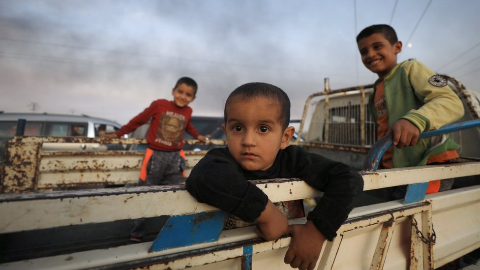 Boys stand at a back of a truck as they flee Ras al Ain town
