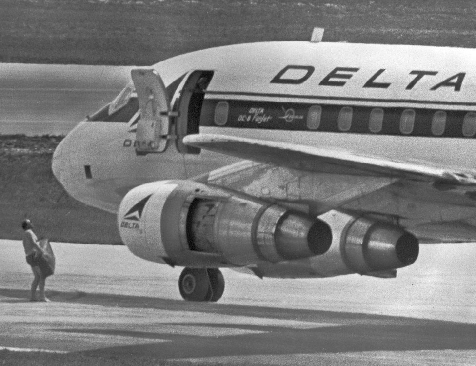 FBI agent carrying suitcase next to Delta airline Flight 841