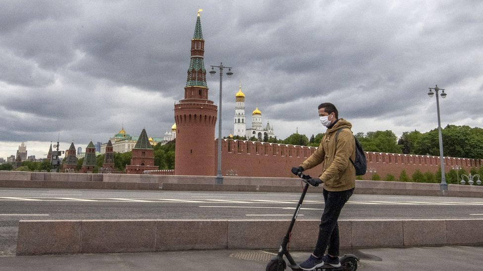 A man on a scooter wearing a face mask outside the Kremlin in Moscow