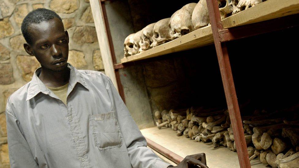 Joven contempla los cráneos de víctimas del genocidio en Ruanda