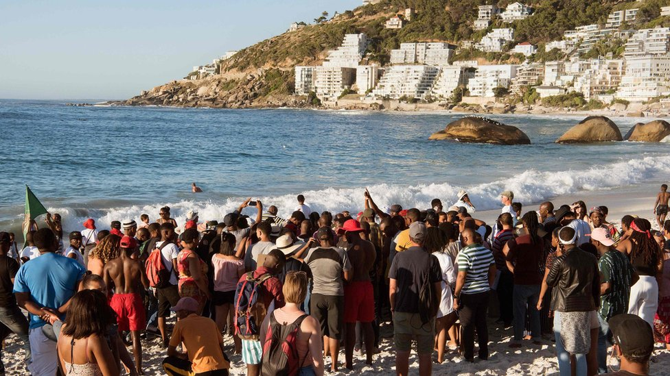Image shows protestors from different political groups take part in a demonstration on Clifton beach on December 28, 2018