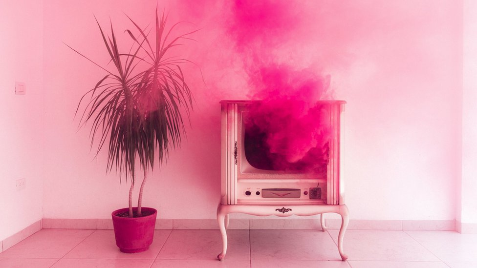 Concept image - a plume of pink smoke coming out from an antique tv set, with a plant next to it