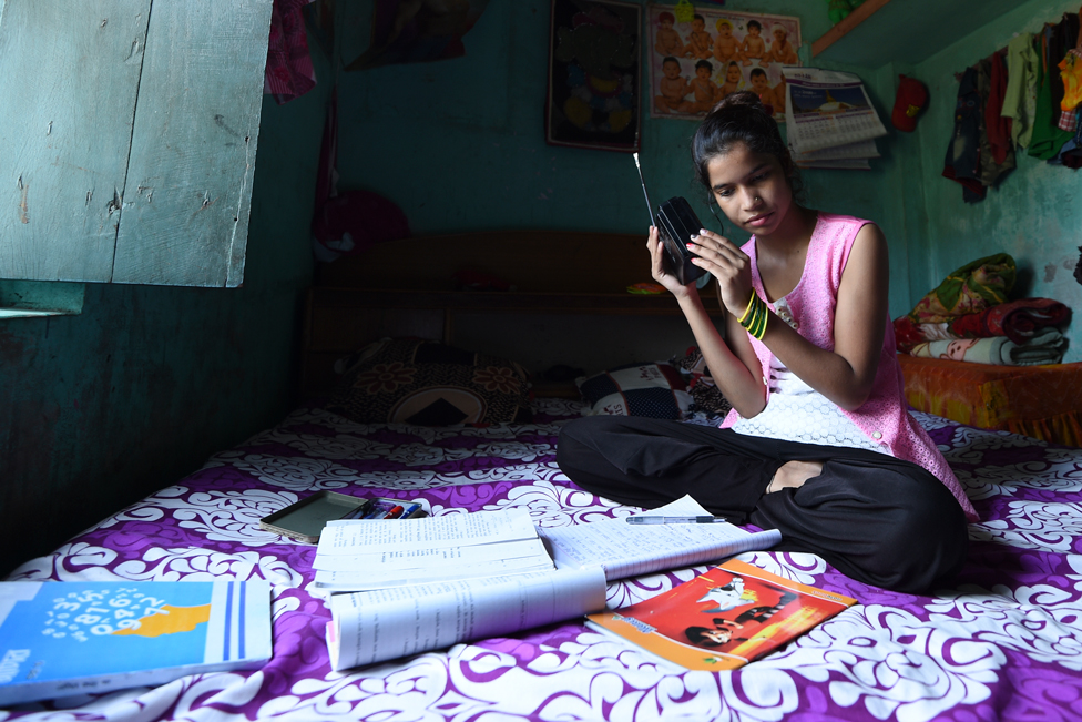 Anjali Patel holding a radio with sheets of paper surrounding her