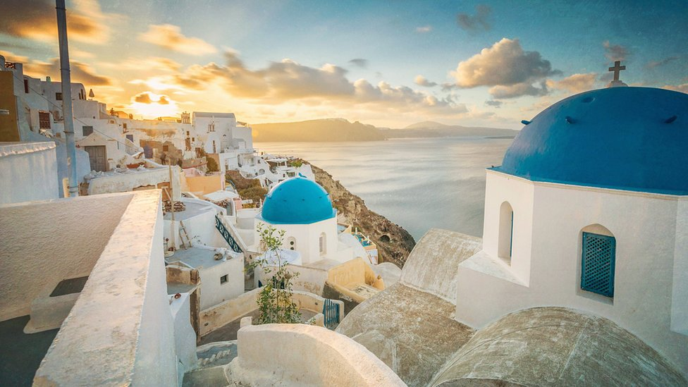 Church And Houses In Town By Sea At Santorini During Sunrise - stock photo