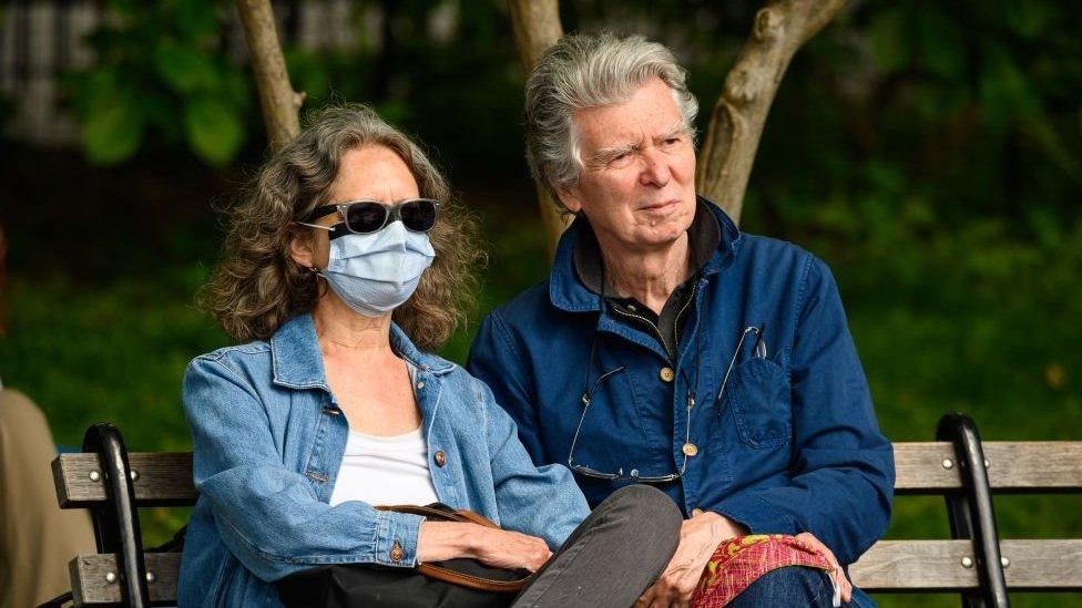 par na klupi - žena s maskom i muškarac bez nje