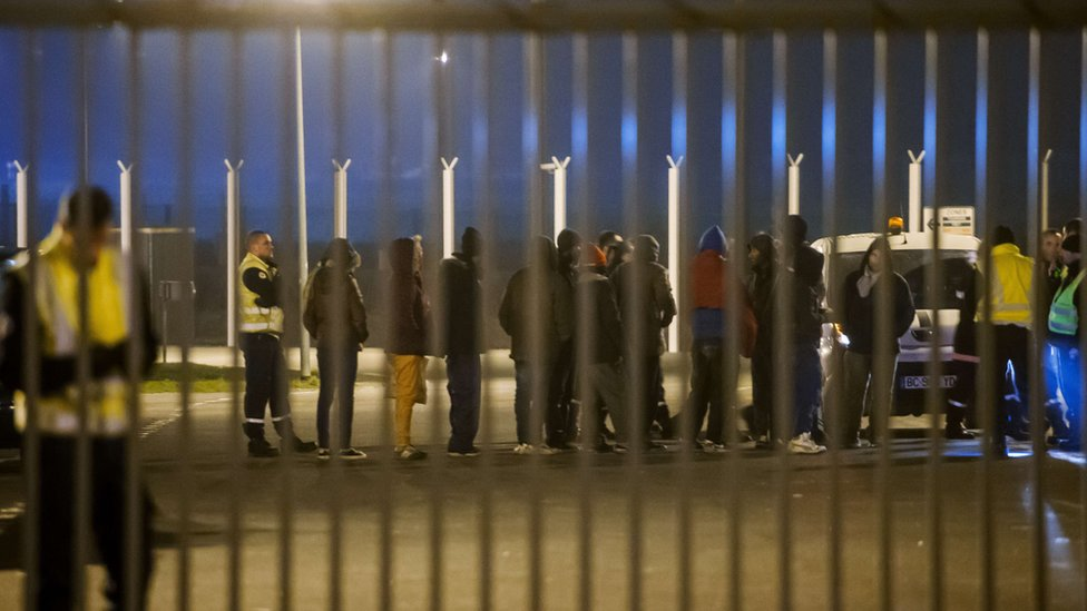 Security staff escort migrants after their incursion into the Eurotunnel site in Coquelles, northern France, on 3 October 2015