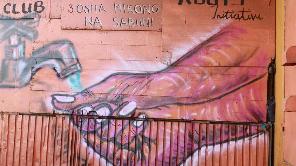 Pintura en una pared de unas manos lavándose las manos.