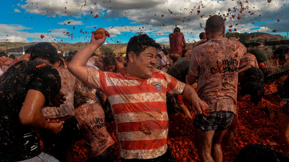 People participate in the tenth annual tomato fight