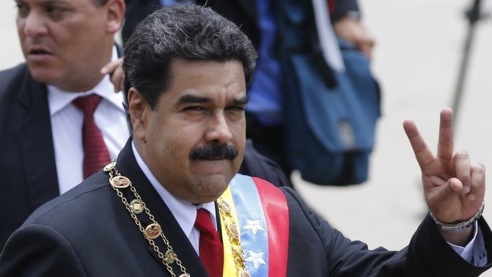 Venezuela's President Nicolas Maduro flashes a victory sign at supporters during a parade marking Venezuela's Independence Day in Caracas, Venezuela, Tuesday, July 5, 2016.