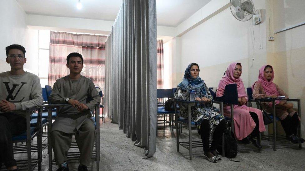 طلاب يحضرون فصلا دراسيا يفصل بستارة بين الذكور والإناث في جامعة خاصة في كابل في 7 سبتمبر/أيلول 2021