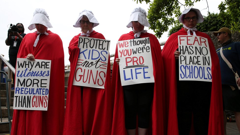 """Activists wear red robes and white bonnets based on """"The Handmaid's Tale"""" before the """"March for Our Lives"""""""