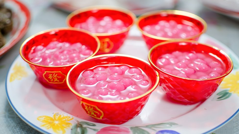 Small red bowls decorated with Chinese inscriptions, and full of brightly coloured tangyuan (sweet dumplings made of glutinous rice and served in syrup)