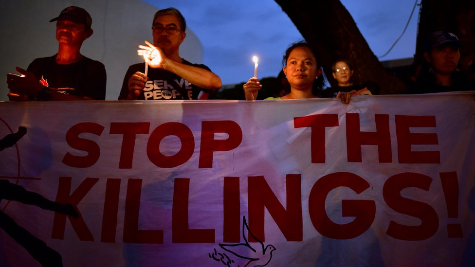 Protesters hold a sign that reads 'Stop the Killings'