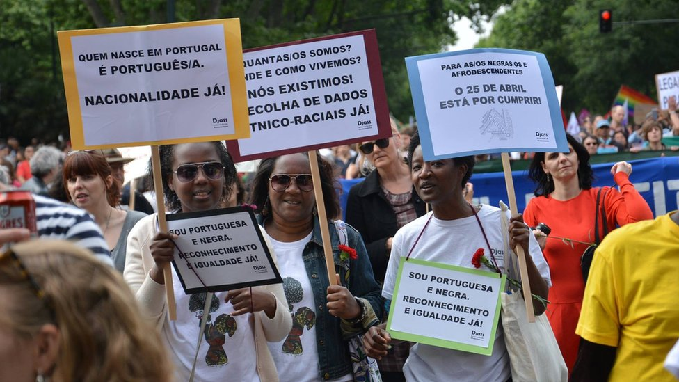A crowd partakes in a march, waving placards, at a parade over Portugal's citizenship rules
