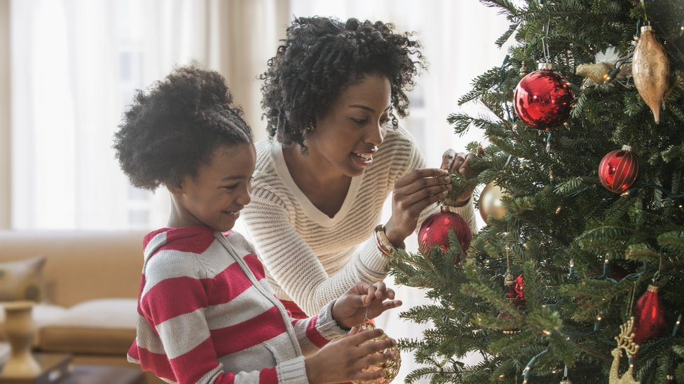 Photo of a mother and daughter near a Christmas tree
