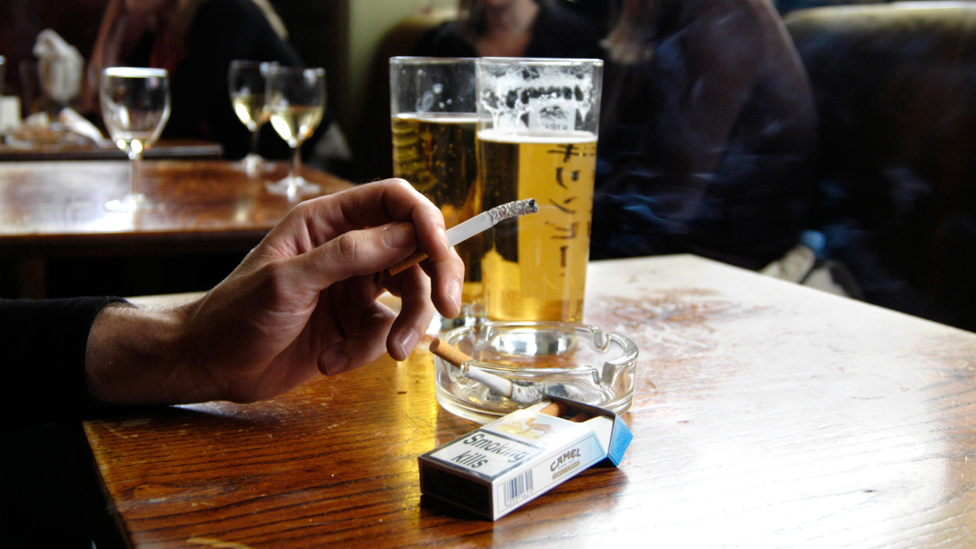 Hand holding a half-smoked cigarette at a pub table, beer glasses in the background